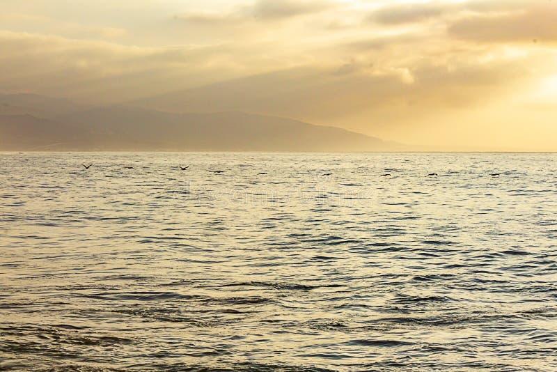 Open oceaanuitgestrektheid bij zonsopgang, met wolken, zonnestralen, watertextuur, en verre heuvels, royalty-vrije stock foto