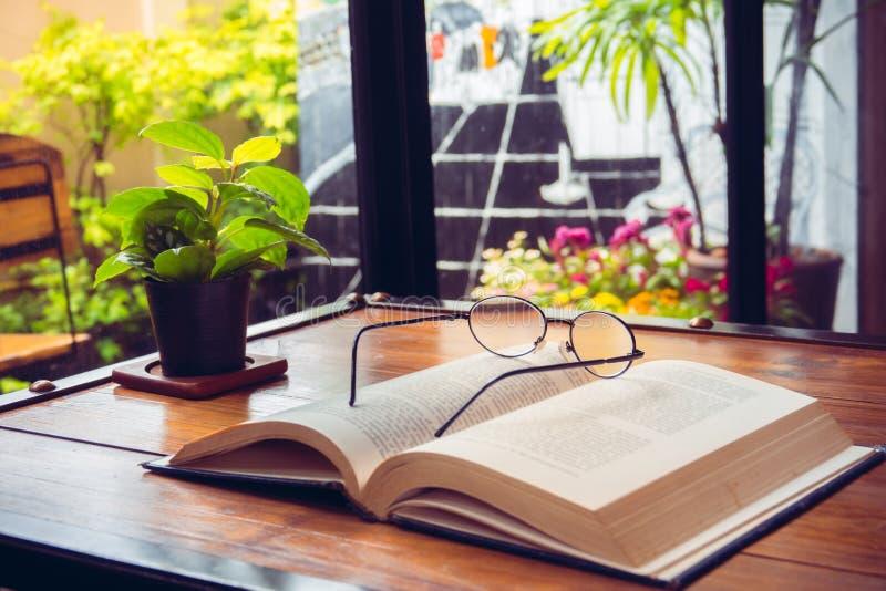 Open oud boek met glazen op houten lijst in koffie stock foto's