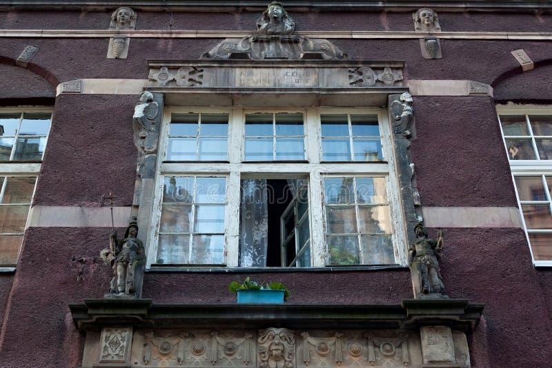 Open oud sjofel venster met bas-hulp op één van de historische gebouwen in de Belangrijkste Stad van Gdansk stock afbeeldingen