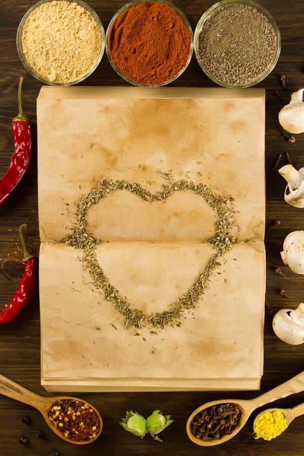 Open oud uitstekend boek met kruiden en hart op houten achtergrond Gezond vegetarisch voedsel royalty-vrije stock fotografie