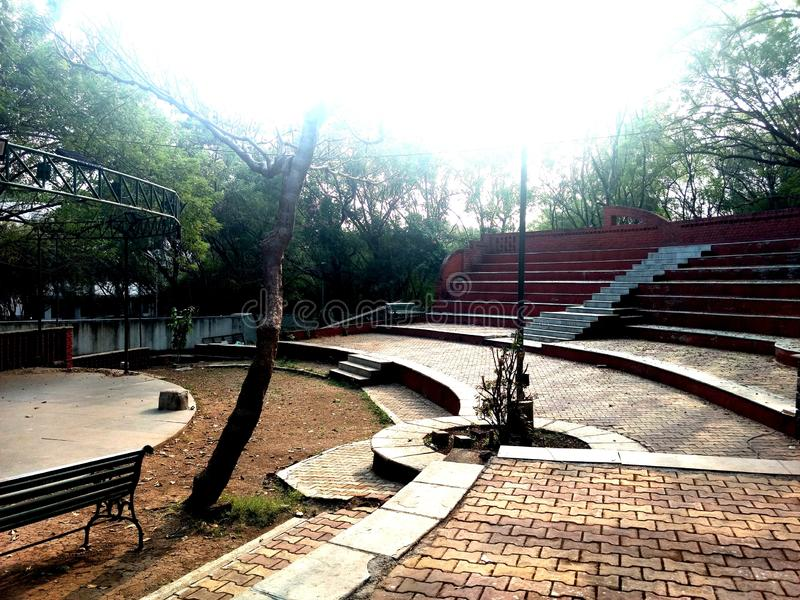 An open theater for students learning Arts and Culture. An open outdoor theater for students of Arts and culture. It is surrounded by trees on all sides. A good stock photo