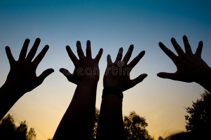 Open palms hands silhouettes against sunset blue sky royalty free stock photo