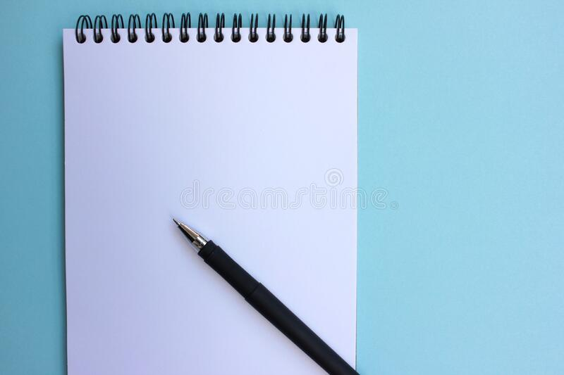 Open paper notebook with a black pen. on blue background. Back to school concept. Flat lay, copy space stock photos