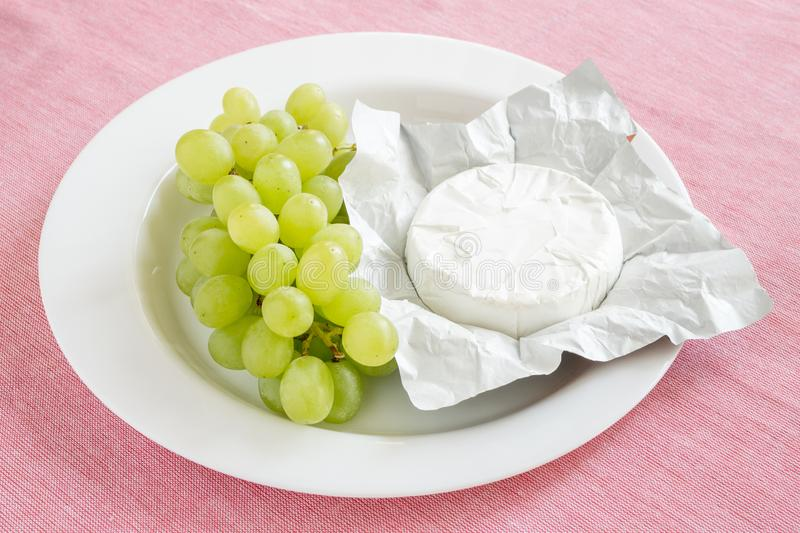Open paper package of whole head of camembert and sweet green grapes on a white plate on a pink tablecloth. Soft cheese covered with edible white mold royalty free stock photo