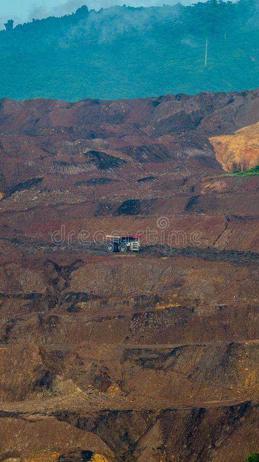 Open pit coal mining, Sangatta, Indonesia. Open pit coal mining in Sangatta, Indonesia. Big truck is used to transport materials in this site stock photography