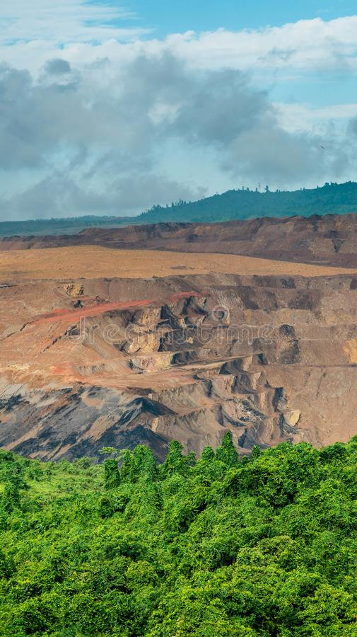 Open pit coal mining, Sangatta, Indonesia. Open pit coal mining in Sangatta, Indonesia with green vegetation as the foreground royalty free stock image