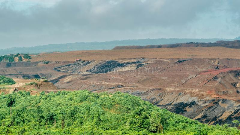 Open pit coal mining, Sangatta, Indonesia. Open pit coal mining in Sangatta, Indonesia with green vegetation as the foregroundn stock photo