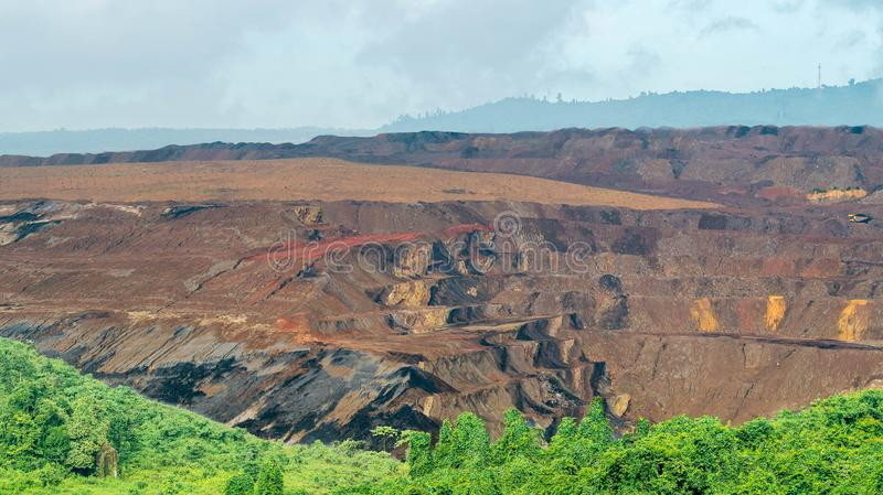 Open pit coal mining, Sangatta, Indonesia. Open pit coal mining in Sangatta, Indonesia with green vegetation as the foreground stock image