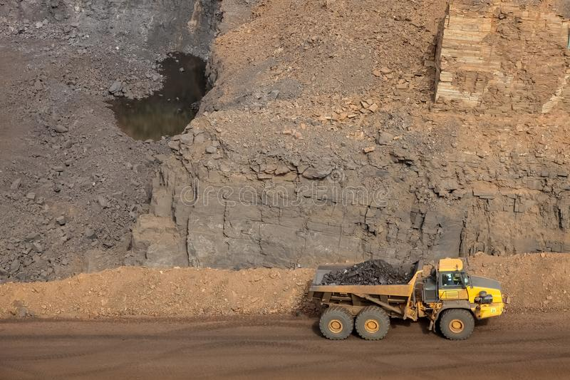 Open pit Manganese Mining. Rock dump truck transporting ore rich rock for processing at open pit mine royalty free stock image