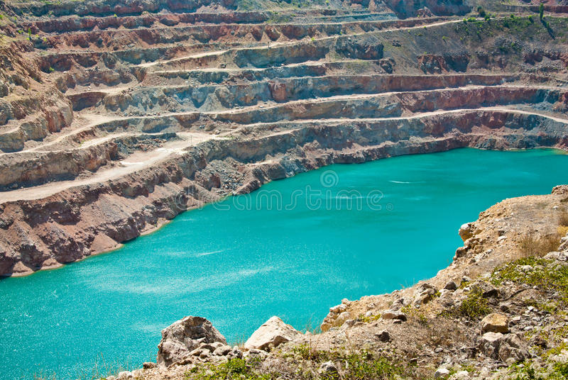 Open pit mine. Abandoned mining exploration. Blue lake in mining industrial crater, acid mine drainage in rock. Open pit mine with lake. Quarry fluxes for the royalty free stock photo