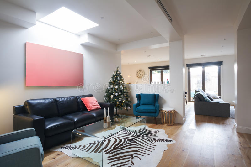 Open plan casual living room in contemporary home. With christmas tree royalty free stock image