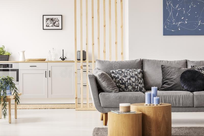 Open plan studio apartment with small white kitchen and living room with grey couch and wooden coffee table royalty free stock photo