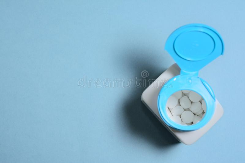Open plastic jar with tablets on a blue background, top view. Open plastic jar with white pills on a blue background, top view royalty free stock photo