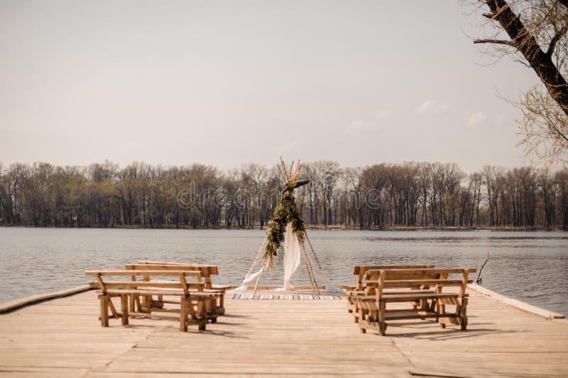Open plek voor Europese huwelijksceremonie met houten banken en met de hand gemaakte die boog met tropische bloemen worden verfra royalty-vrije stock afbeeldingen