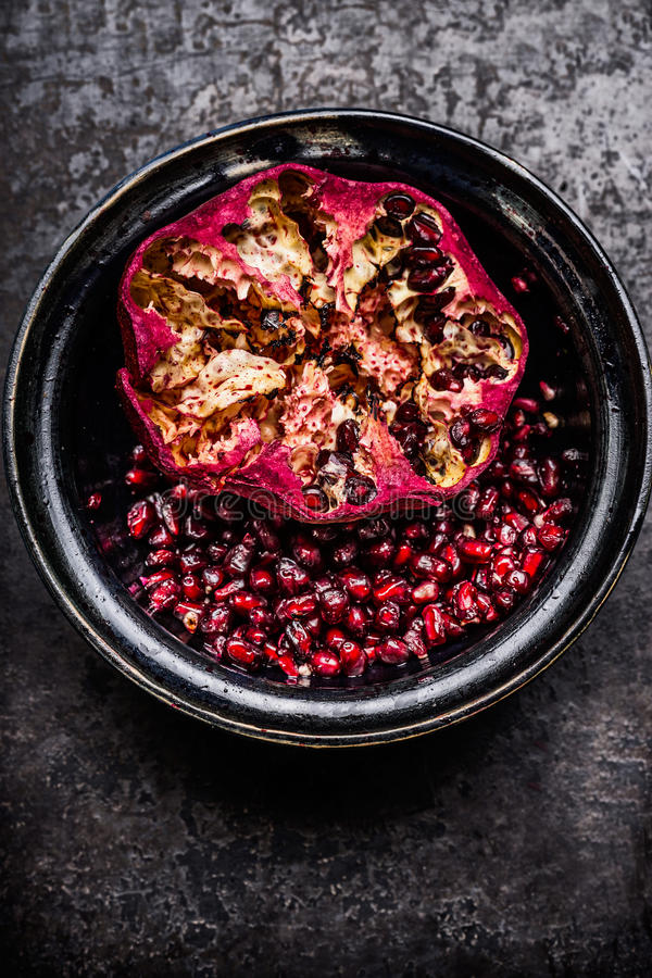 Open pomegranate with seeds and peel in rustic bowl, top view. royalty free stock photo