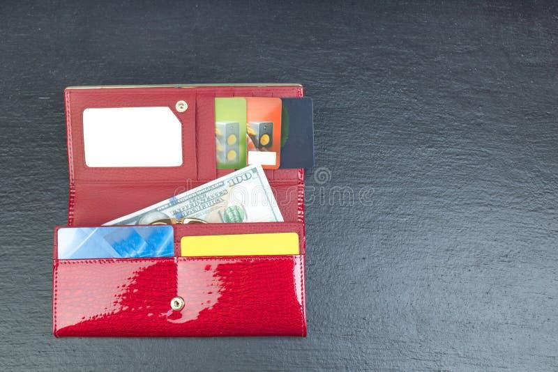 Open portefeuille met betaalpassen en dollarrekeningen stock foto
