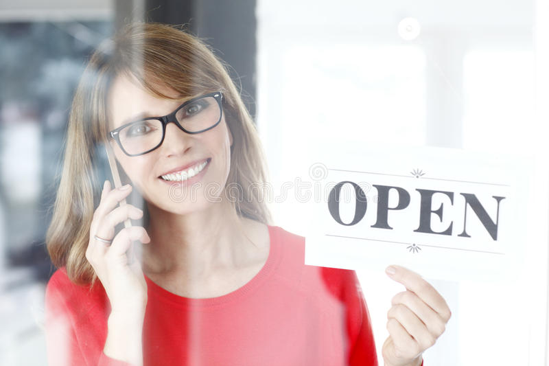 We are open. Portrait of middle age small shop owner woman holding in her hand open sign and making call while standing at doorway stock photography