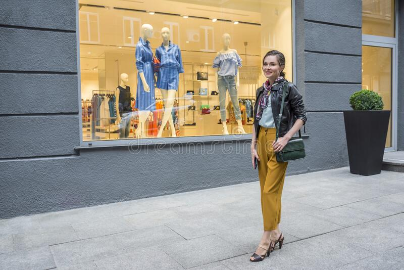An open portrait of a young stylish woman walking in the street. Shopping. A concept of beauty and fashion royalty free stock photography
