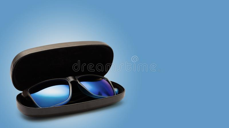 Open protective case with sunglasses. on color background.  royalty free stock photography