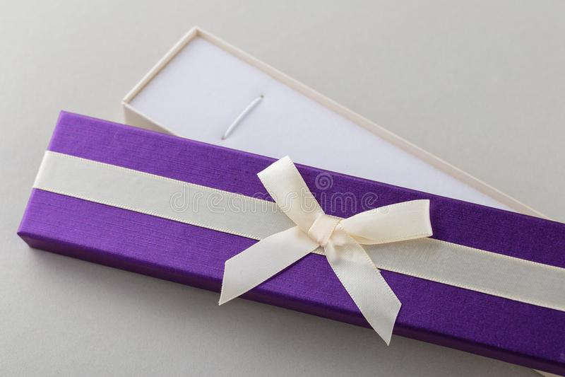 Open purple gift box with ribbon bow on gray background royalty free stock images