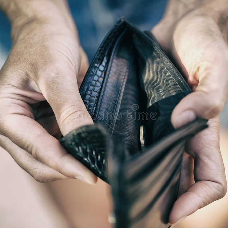 Open purse with one coin inside as a sign of lack of mo. Open purse with one coin inside close-up as a sign of lack of money royalty free stock image