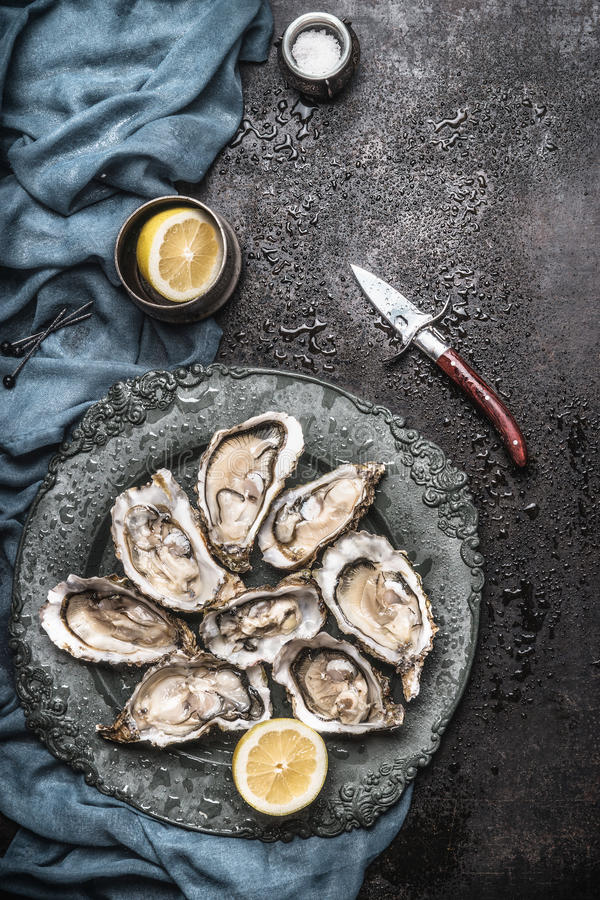Open raw oysters on vintage plate with lemon and oysters knife, dark rustic background with water drops. Top view royalty free stock photos