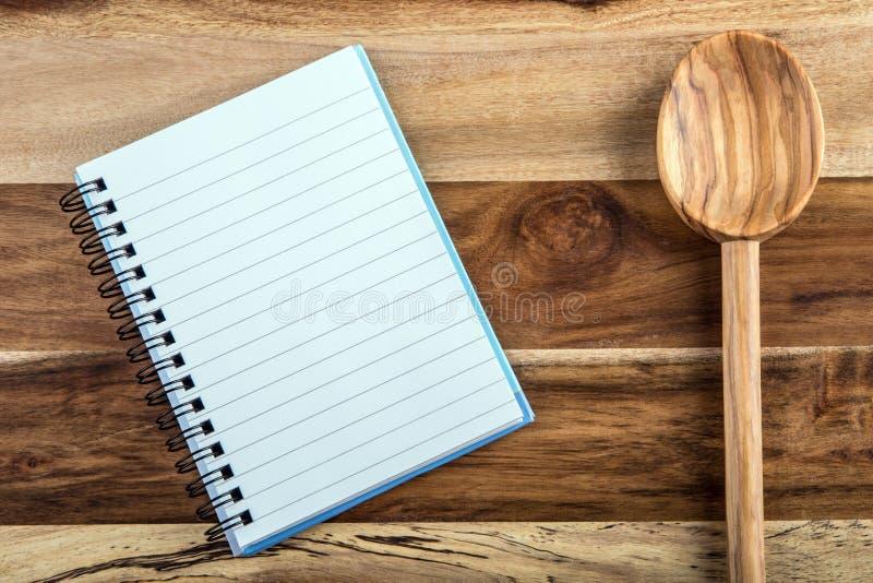Open receptenboek - notitieboekje en houten lepel op houten achtergrond royalty-vrije stock fotografie