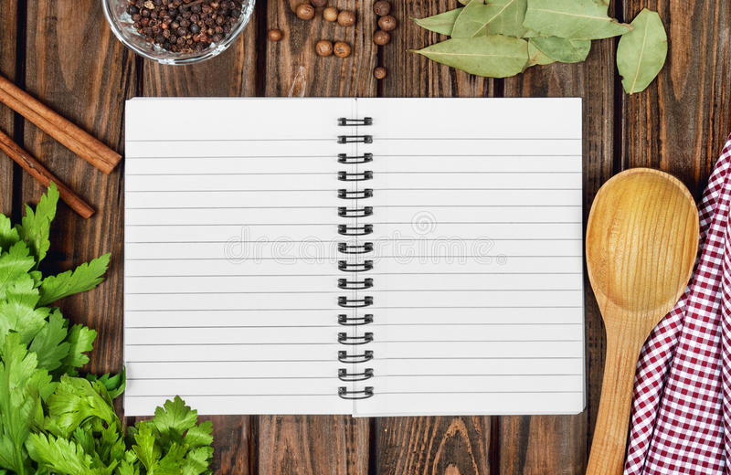 Open recipe book with fresh herbs and spices royalty free stock photos
