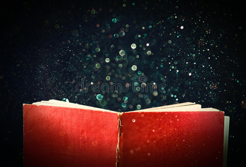 Open red book and glowing glittering lights.  stock photography