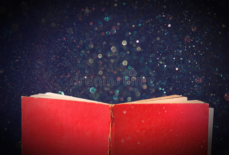 Open red book and glowing glittering lights. Open red book and glowing glittering lights stock photo