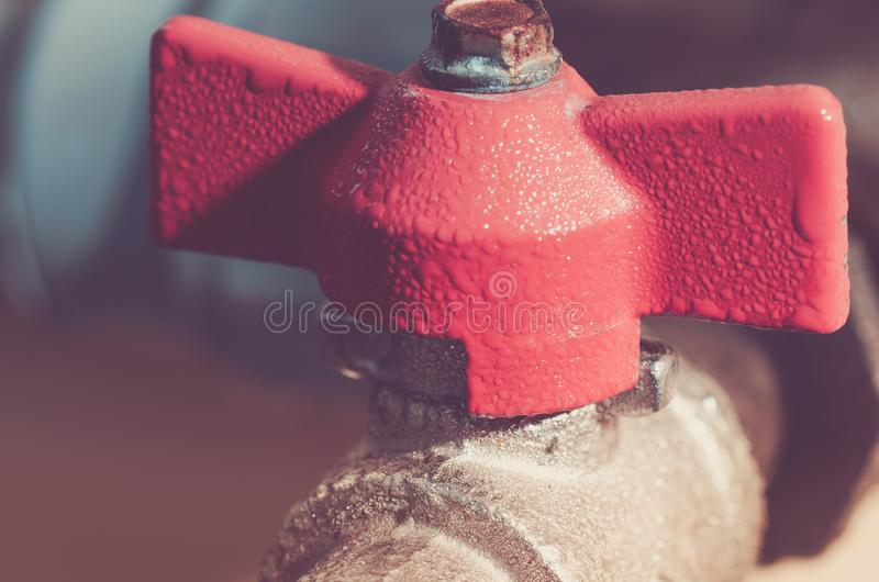 Open red valve water/crane with the gate for water. Toned stock photo