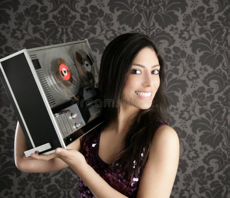 Open reel tape recorder beautiful brunette Dj. Retro open reel tape recorder beautiful brunette Dj hearing music gray walpaper stock photos