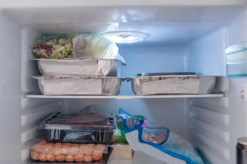 Open refrigerator filled with raw food, vegetables and foil pack stock photo