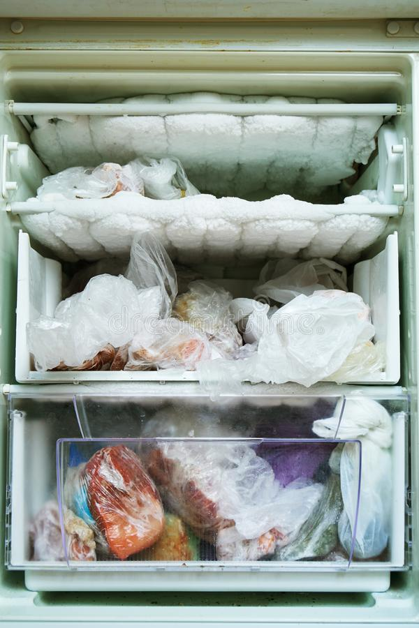 Open refrigerator with a freezer which has not been defrosted for a long time full of food and lots of frozen ice royalty free stock image