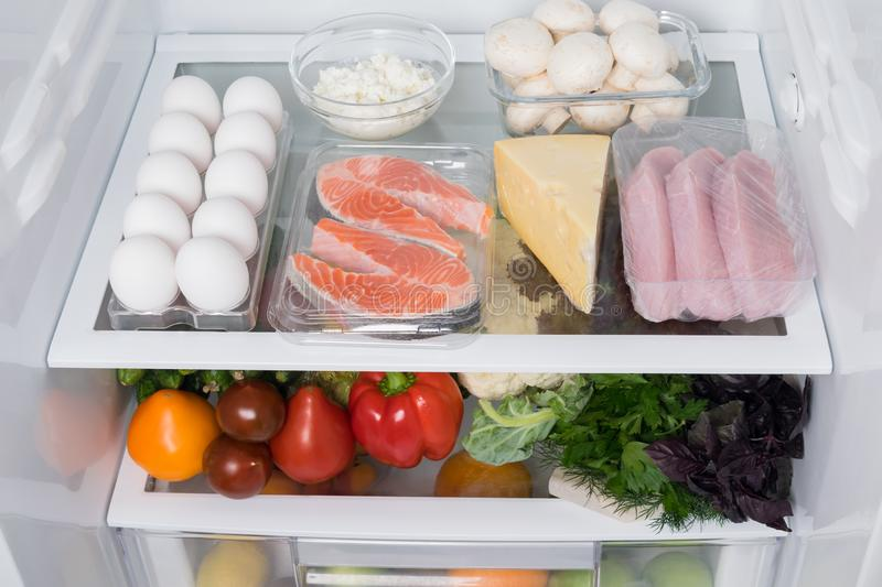 In the open refrigerator on the shelf meat and vegetables, close-up front view royalty free stock image