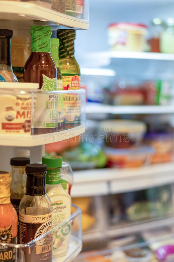 Open refrigerator stocked with a variety of fresh foods and condiments royalty free stock photography