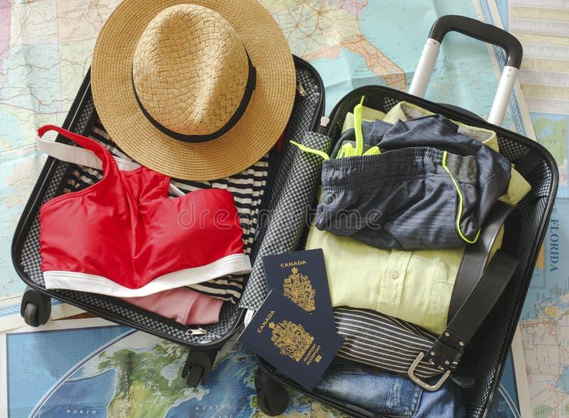 Open reizigers` s zak met kleding, toebehoren, en paspoort Reis en vakantiesconcept stock fotografie