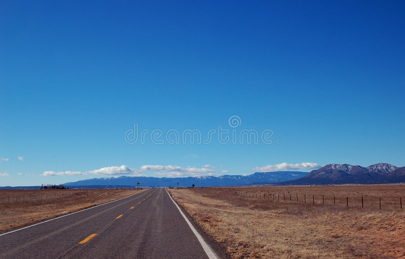 The Open Road. Empty road stretching to the horizon in rural New Mexico stock photography