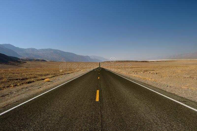 The open road and blue sky of Death Valley National Park, California - USA royalty free stock photography