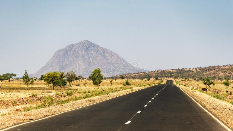 An open road in Ethiopia. Long straight road through ethiopian landscape royalty free stock image