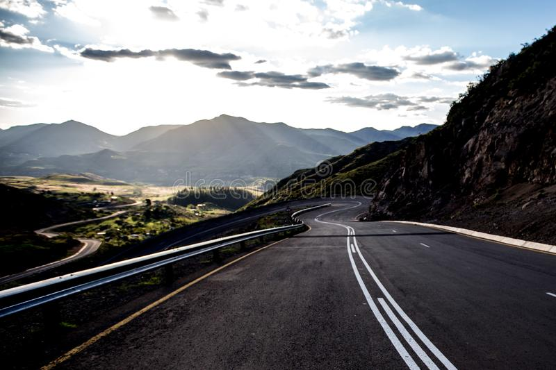 Open road high in the mountains. Of South Africa. Endless mountains on the horizon and the sun beaming down through the clouds onto golden grass land royalty free stock photos