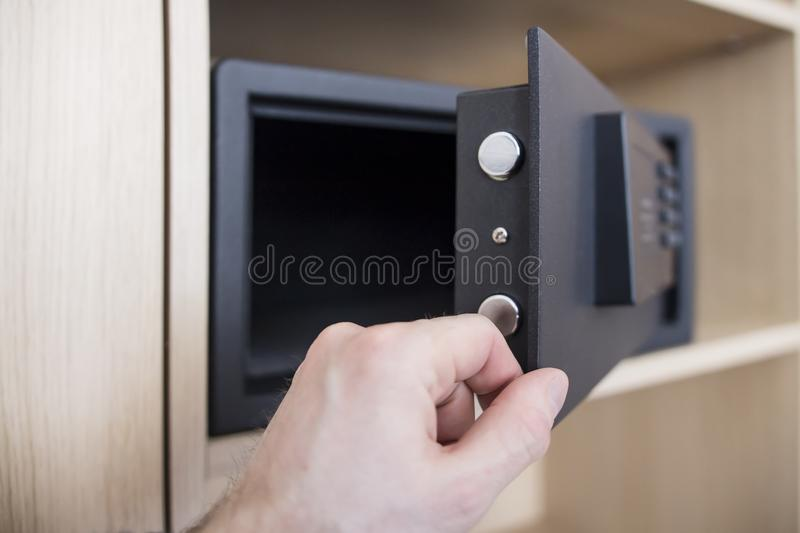 Open safe door with electronic lock close up. Keep money and jewelry at home. man`s hand and safe in the apartment. stock photography