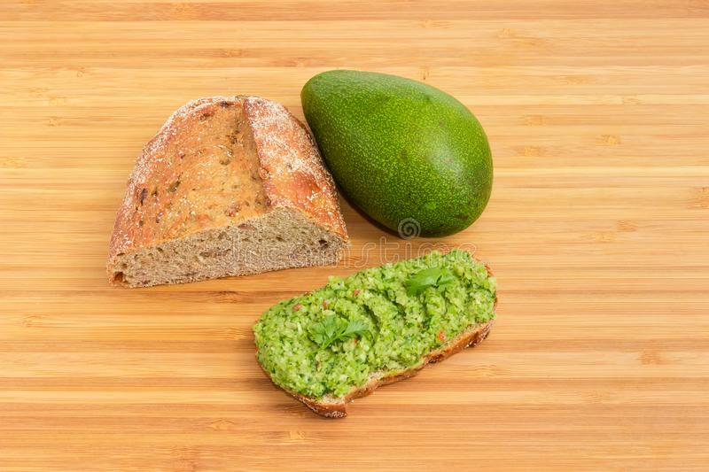 Open sandwich with guacamole, avocado and brown sprouted bread. Open sandwich with guacamole, whole green-skinned avocado fruit and part of brown bread with stock photos