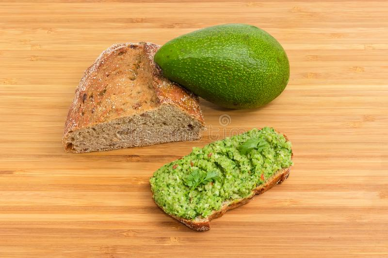 Open sandwich with guacamole, avocado and brown sprouted bread. Open sandwich with guacamole, whole green-skinned avocado fruit and part of brown bread with royalty free stock images