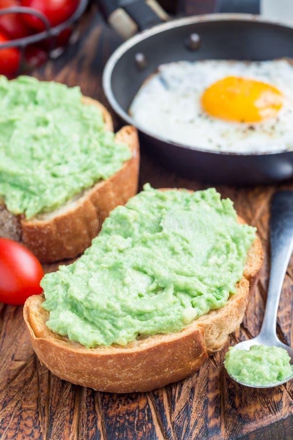 Open sandwich met fijngestampte avocado op geroosterd brood, gebraden ei in pan op verticale achtergrond, gezond ontbijtconcept royalty-vrije stock afbeeldingen