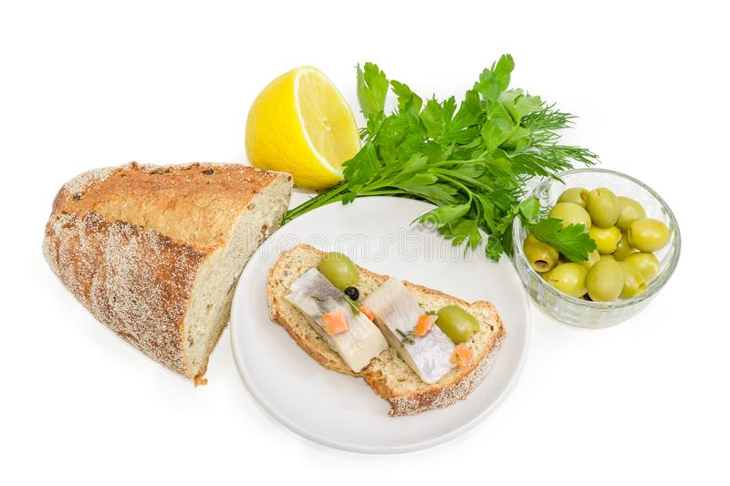 Open sandwich with pickled herring, olives and brown sprouted br. Open sandwich made of brown sprouted bread, slices of fillet of pickled Atlantic herring and royalty free stock image