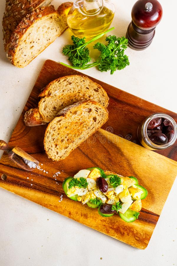 Open sandwich with traditional German potato salad, bread, ingredients on wooden cutting board, top view stock photo