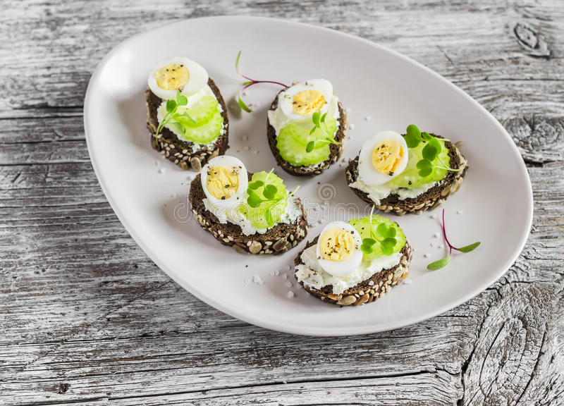 Open sandwiches with cream cheese, quail eggs and celery. Delicious healthy Easter snack royalty free stock photography