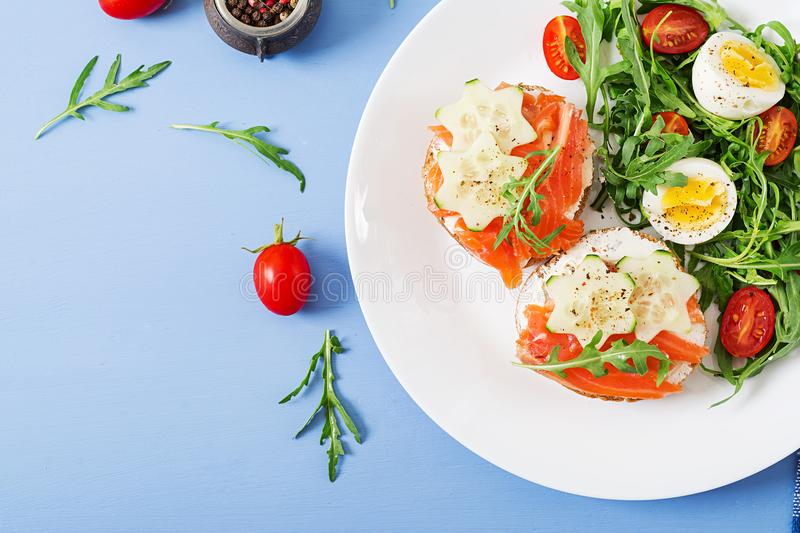 Open sandwiches with salmon, cream cheese and rye bread. Tasty breakfast. Open sandwiches with salmon, cream cheese and rye bread in a white plate and salad with stock photography