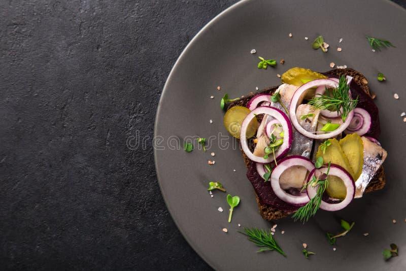 Open sanwich met donker roggebrood, biet, marineerde haringen, pickl royalty-vrije stock foto